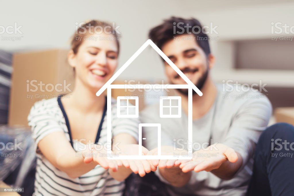 Young couple holding their new, dream home in hands royalty-free stock photo