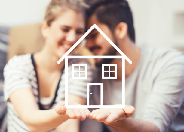 Young couple holding their new, dream home in hands stock photo
