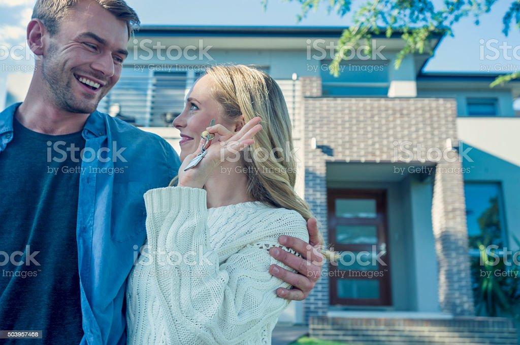 Jovem casal segurando sua nova chave da casa. - foto de acervo