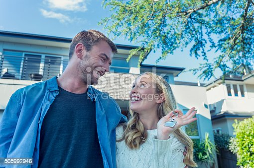 Young couple holding their new house key. They are standing in front of the home in casual clothes. Both are happy, relaxed and smiling. He has a beard and she is blonde. They could be buying or selling real estate. They are looking at each other. Copy space