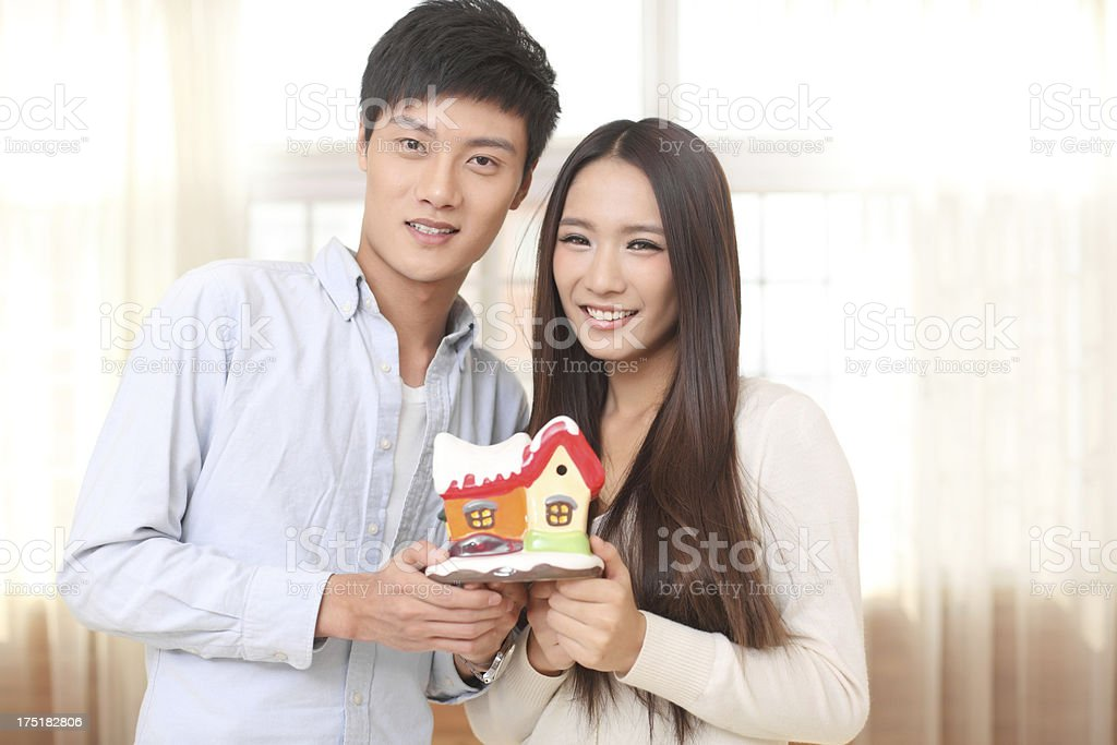 Young Couple Holding Up a Model Home royalty-free stock photo