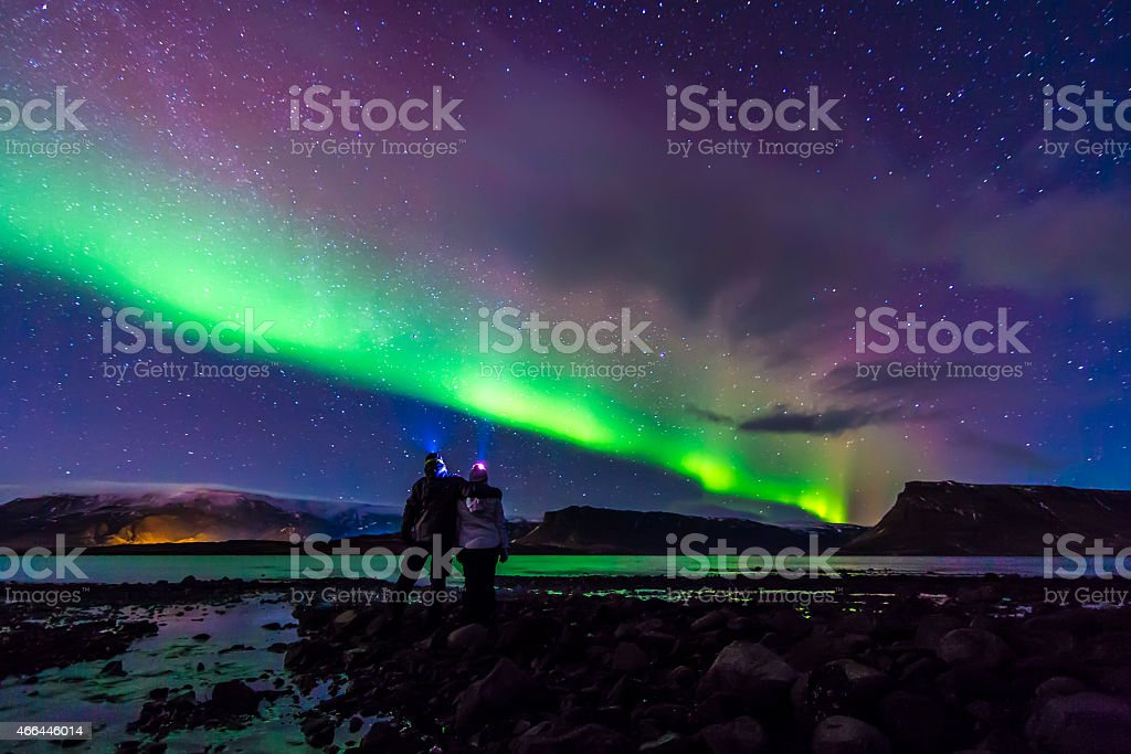 Young Couple hugged under Northern lights Aurora Borealis in Iceland stock photo