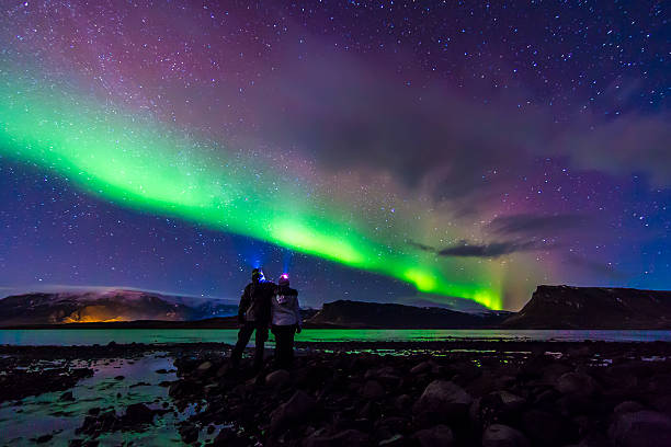 Young Couple hugged under Northern lights Aurora Borealis in Iceland Young adventurist couple hugged while gazing in the dark night sky under the spectacular celestial lights Aurora Borealis, which makes Iceland popular spot for tourist willing to witness one of the greatest natural phenomenon. Shot with Canon EOS, wide angle lens, f2.8, long exposure. lenticular cloud stock pictures, royalty-free photos & images