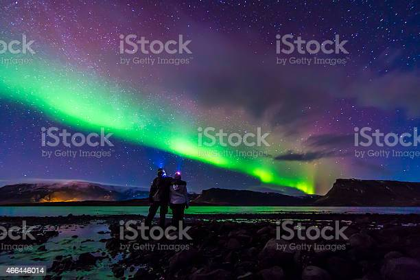 Photo of Young Couple hugged under Northern lights Aurora Borealis in Iceland