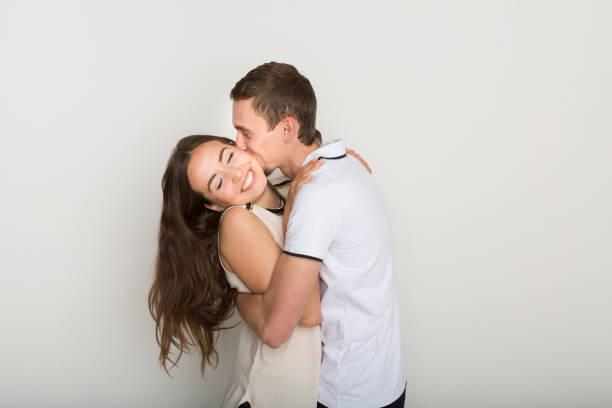 junge paar umarmen und küssen - emoticon hug stock-fotos und bilder