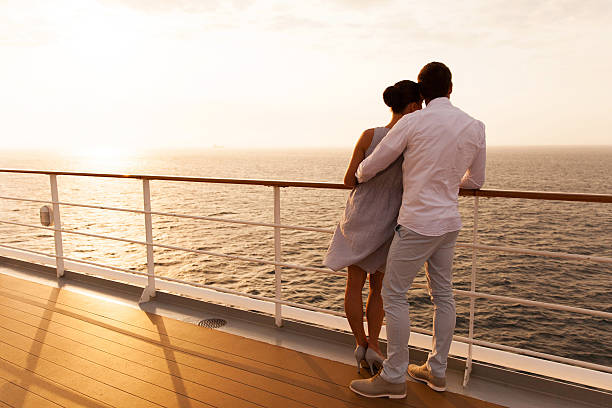 young couple hugging at sunset on cruise ship stock photo