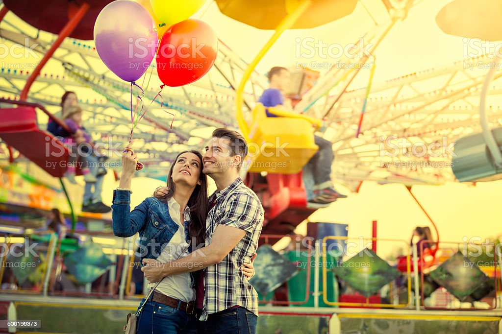 Young couple hugging in amusement park stock photo