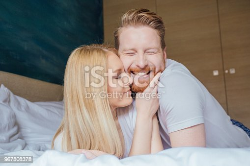 888274920 istock photo Young couple hugging in bed 967808378