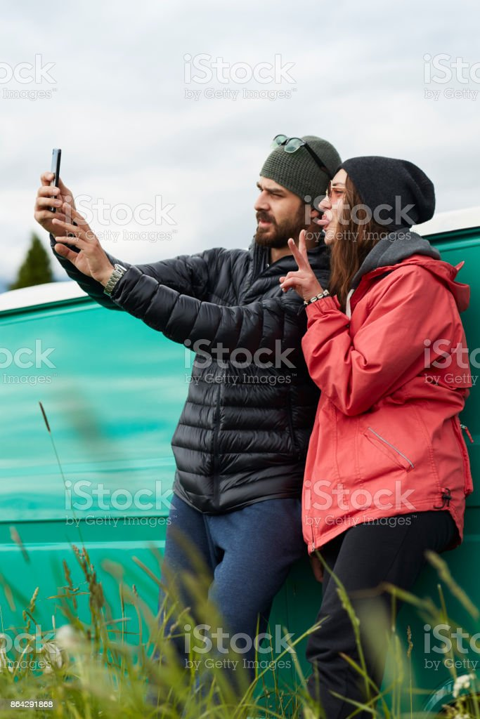 Young couple hugging in front of a camper. Taking selfie. Mountainous landscape royalty-free stock photo