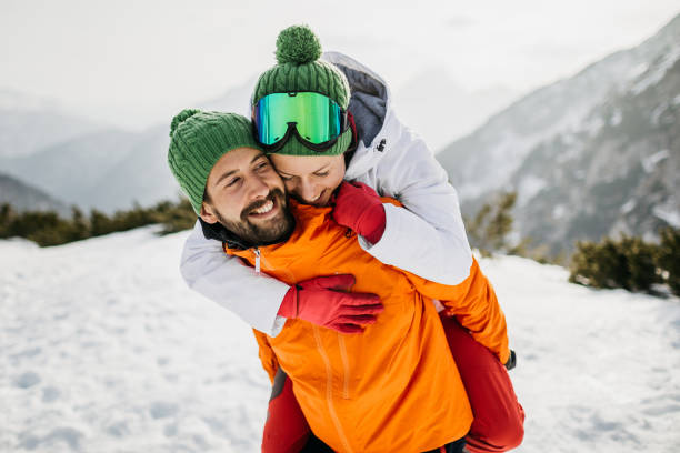 Young couple hugging on snow stock photo