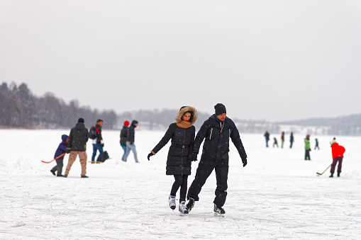 Young couple Ice skating on rink in snow covered Trakai
