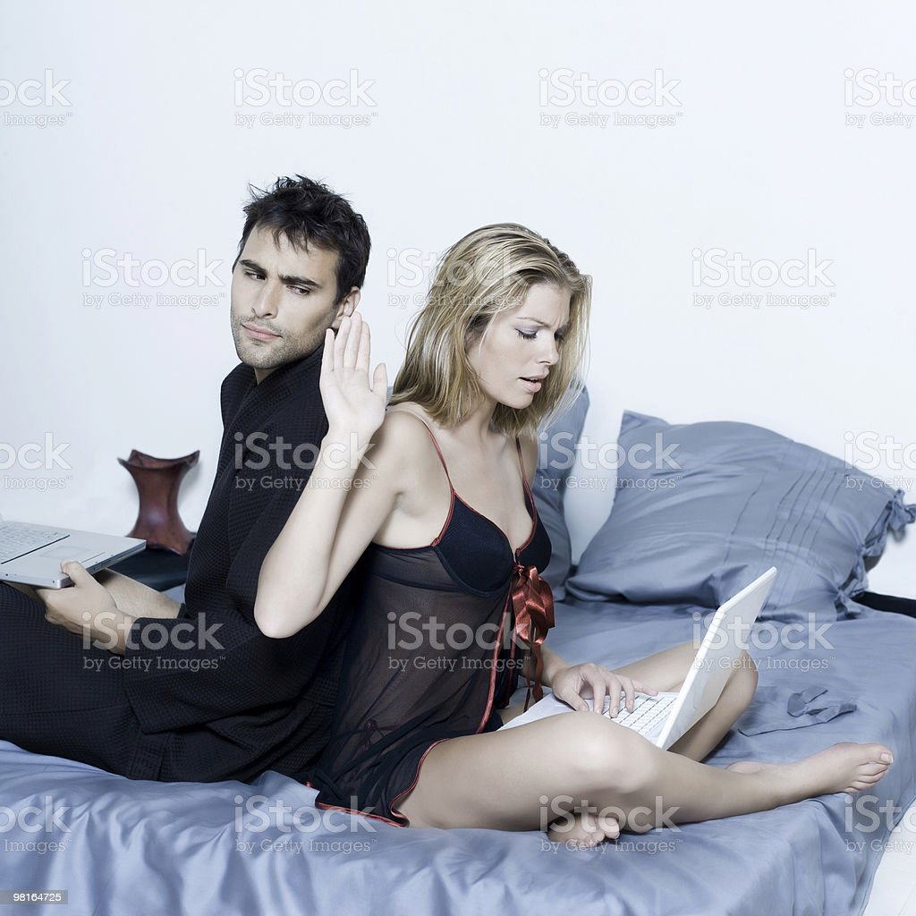 young couple in a bed computing computer laptop royalty-free stock photo