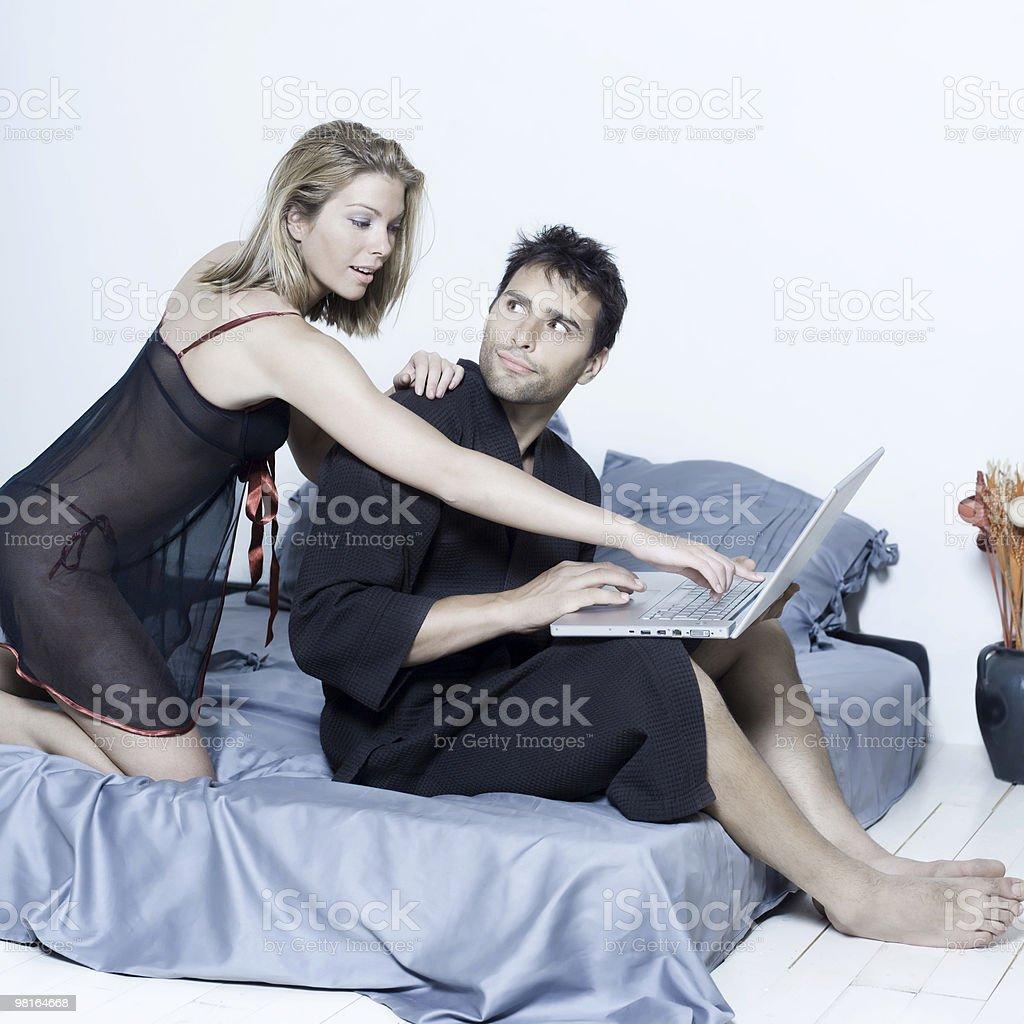 Giovane coppia in un letto di elaborazione portatile scegliendo foto stock royalty-free