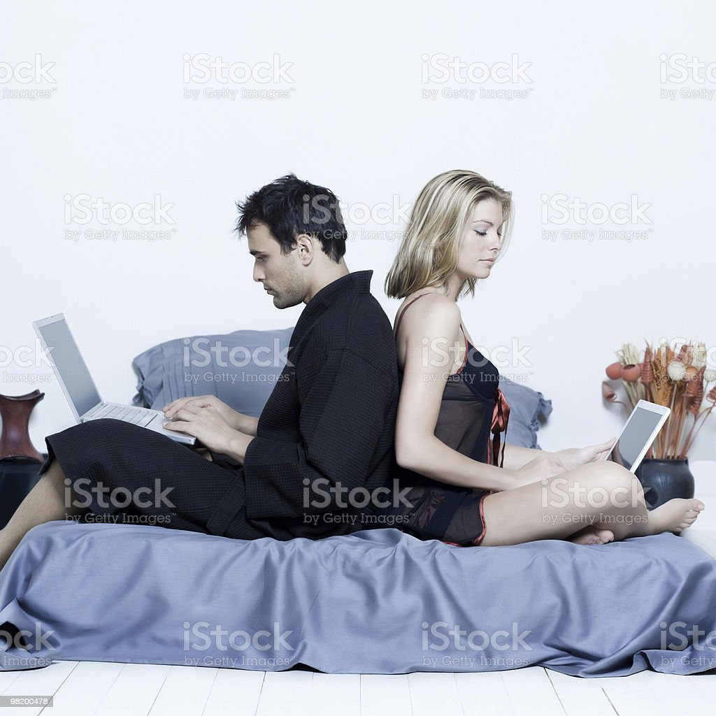 young couple in a bed computing royalty-free stock photo