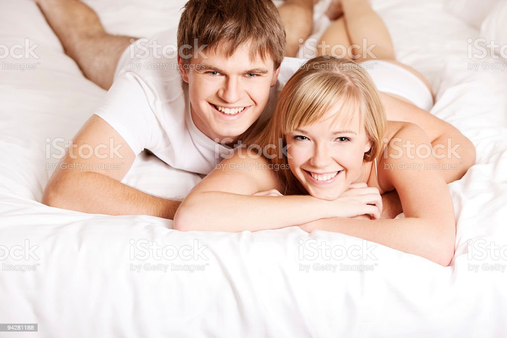 Young couple in a bed (XXXL size) stock photo