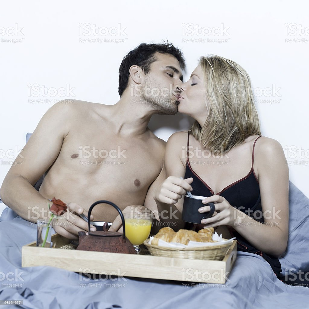 young couple in a bed with breakfast kissing royalty-free stock photo