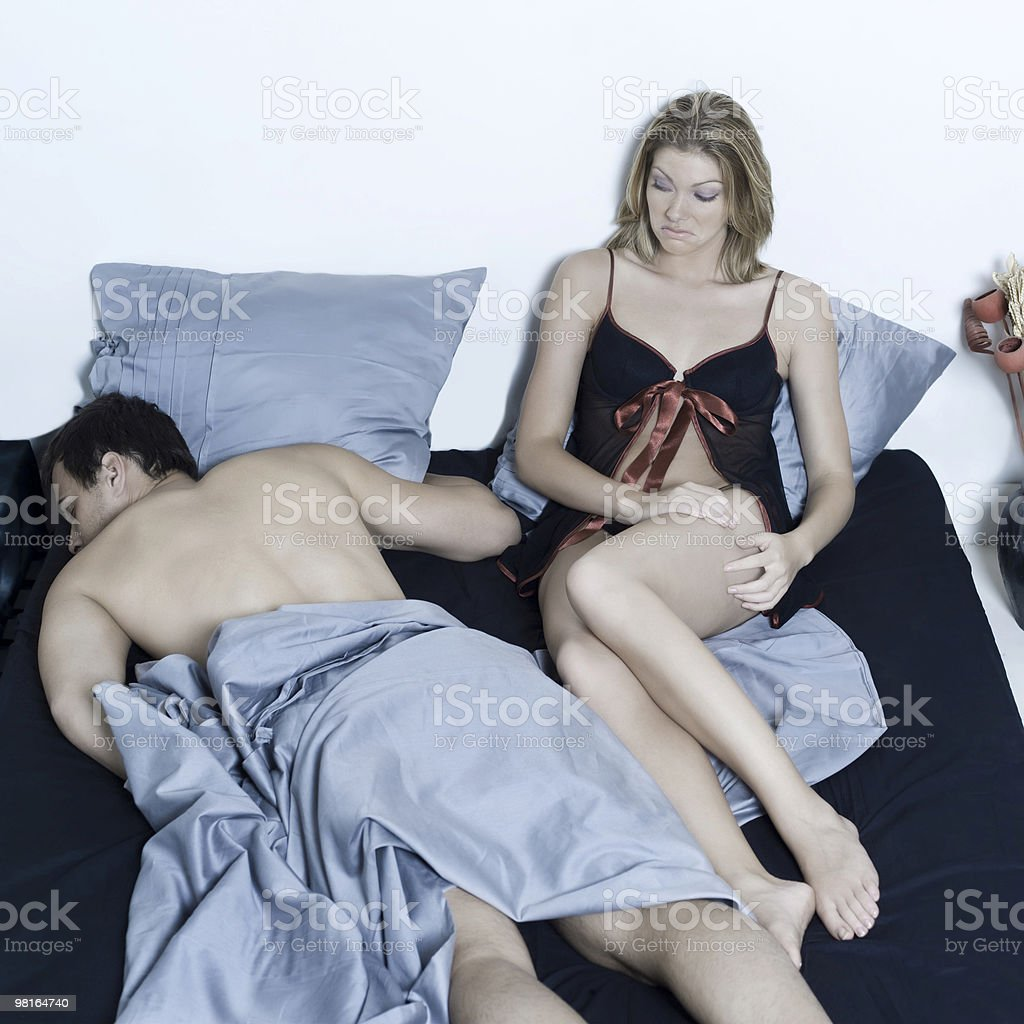 young couple in a bed with woman disapointed man sleeping royalty-free stock photo