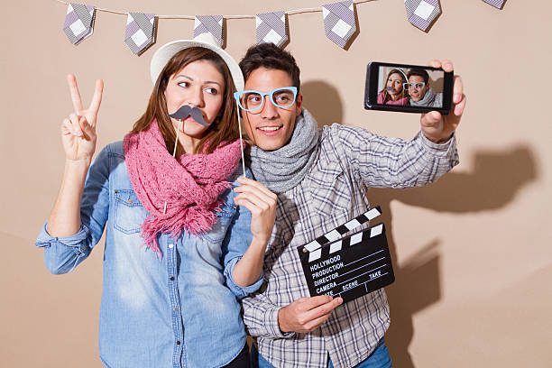 Young couple in a Photo Booth party with gesture face stock photo