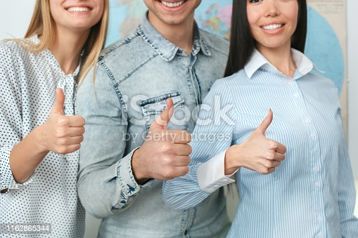 istock Young couple in a tour agency communication with a travel agent travelling concept standing together unity close-up 1162865344