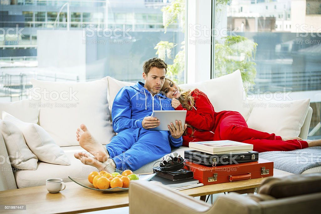 Young couple in an apartment Young couple lying down on sofa in their apartment and using a digital tablet together.  20-24 Years Stock Photo