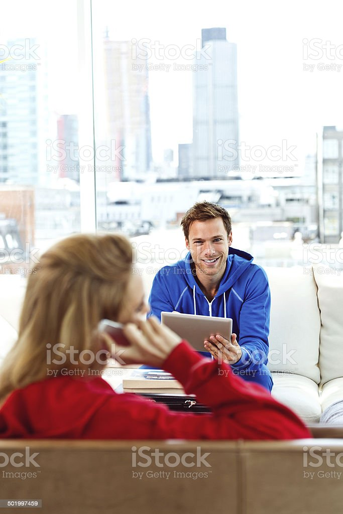 Young couple in an apartment Focus on the young man sitting on sofa in an apartment and using a digital tablet while a young woman talking on phone. 20-24 Years Stock Photo
