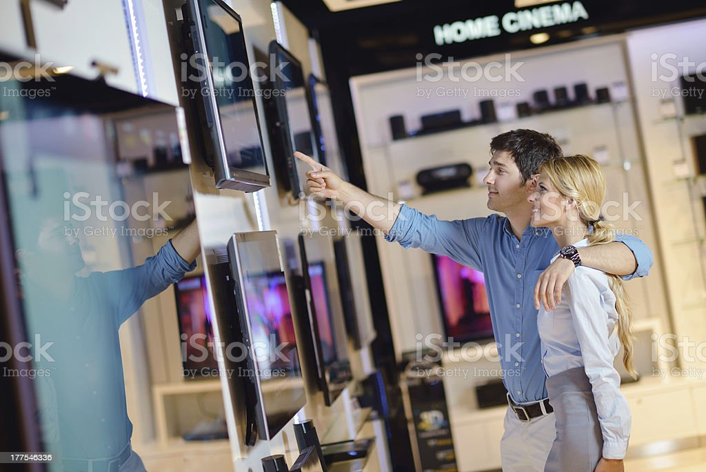 Young couple in an electronics store pointing at a TV stock photo