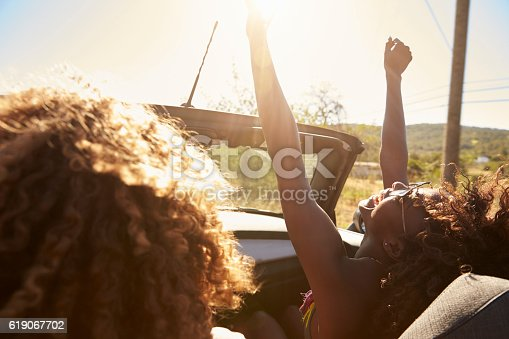 istock Young couple in an open top car, woman with arms raised 619067702