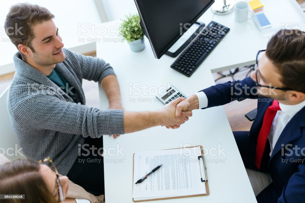 Young couple in bank office shaking hand to financial adviser. - Royalty-free Adult Stock Photo