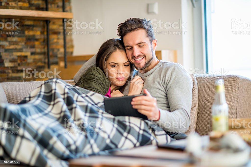 Joven Pareja en la cama con tablet entretenimiento foto de stock libre de derechos