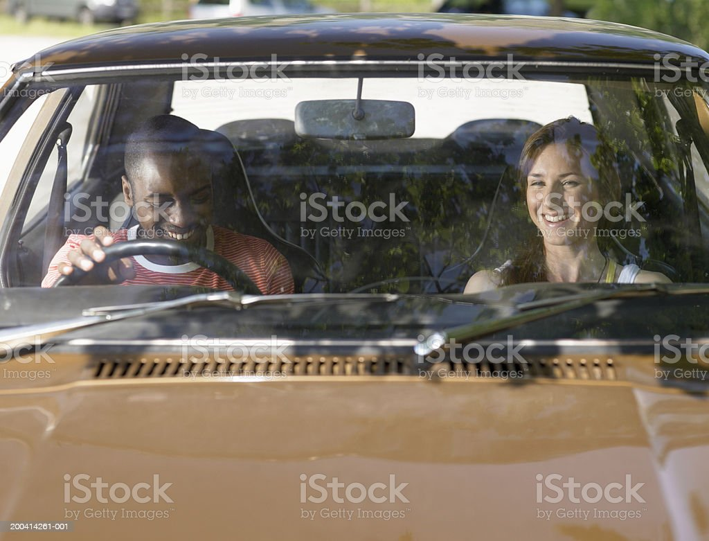 Young couple in car, smiling, view through windscreen royalty-free stock photo