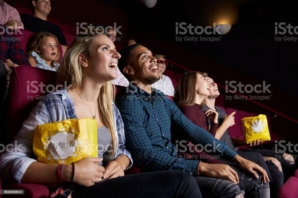 Young Couple In Cinema Watching Film And Eating Popcorn stock photo