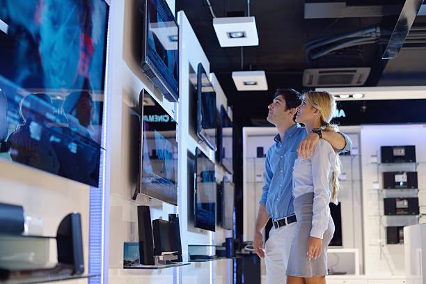 junges paar in die consumer electronics store kaufen-fernseher - freizeitelektronik stock-fotos und bilder