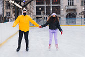Young man in yellow jacket and a woman with curly hair wearing protective face masks feeling happiness having a bright weekend ice-skating on the ice rink together