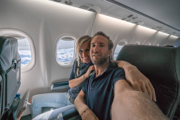 Young couple in flight taking selfie portrait excited to go on vacation stock photo
