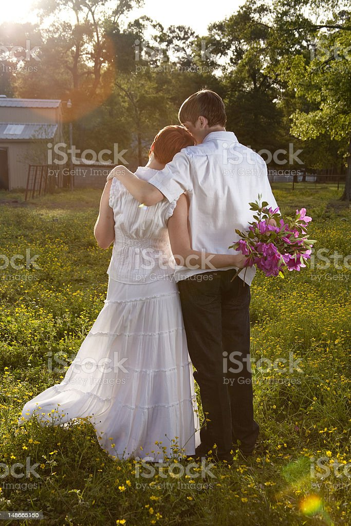 Young couple in flower field she holds bouquet royalty-free stock photo