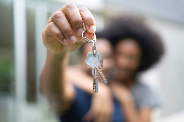 young couple in front of a house, holding keys of their new home - buy a house key imagens e fotografias de stock