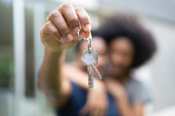 年輕夫婦在一所房子前, 拿著他們新家的鑰匙 - 鎖匙 個照片及圖片檔