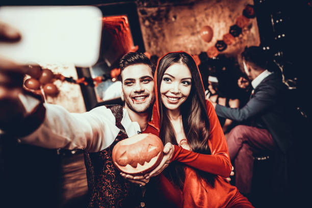 Young Couple in Halloween Costumes taking Selfie Young Couple in Halloween Costumes taking Selfie. Beautiful Woman and Handsome Young Man Wearing Costumes holding Pumpkin at Halloween Party in Nightclub. Friends having Fun Celebrating Halloween costume stock pictures, royalty-free photos & images