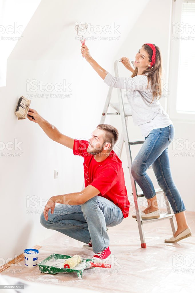 Smiling young couple involved in home improvement works