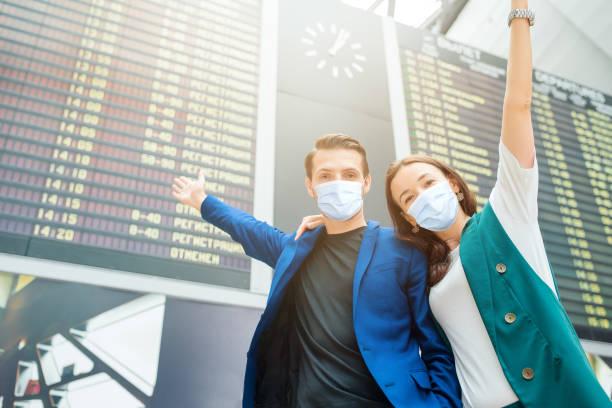 Junges Paar am internationalen Flughafen mit Blick auf die Fluginformationstafel – Foto