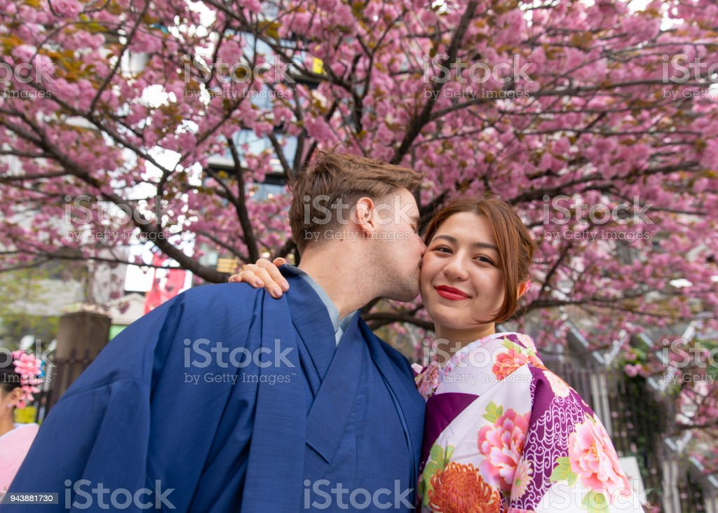 Young couple in kimono kissing under cherry tree stock photo