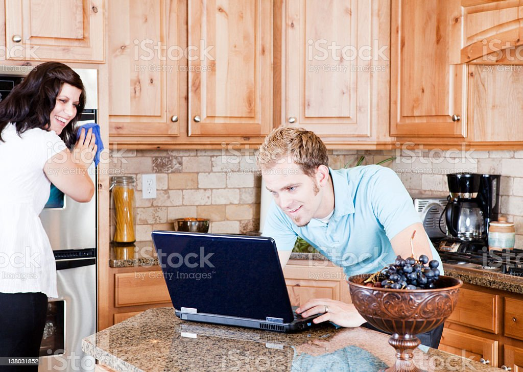 Young Couple in Kitchen Cleaning and Using Computer royalty-free stock photo
