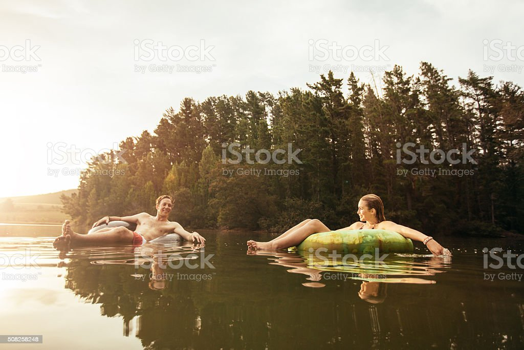 Young couple in lake on inflatable ring stock photo