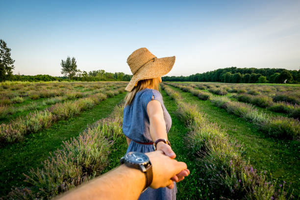 Young couple in lavender field at sunset stock photo