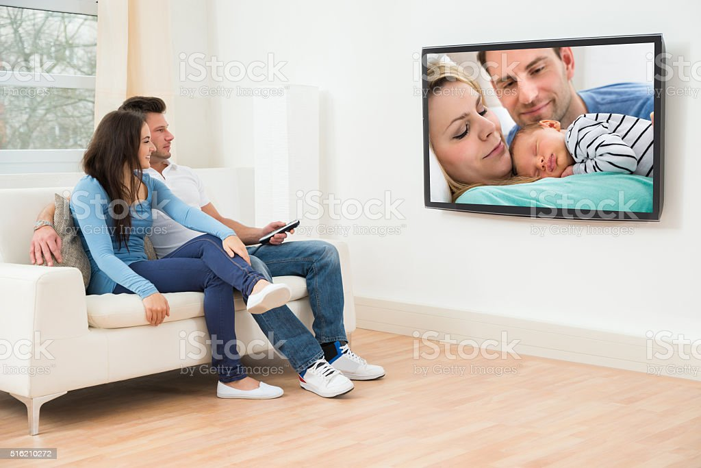Young Couple In Livingroom Watching Television stock photo