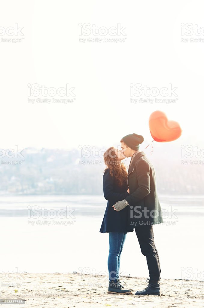 Young couple in love at the riverside, kissing stock photo