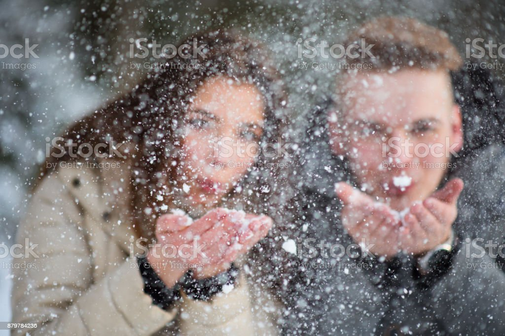 Young couple in love blowing snow away stock photo