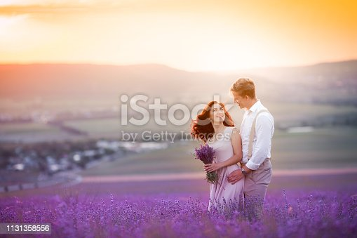 istock Young couple in love bride and groom, wedding day in summer. Enjoy a moment of happiness and love in a lavender field. Bride in a luxurious wedding dress. 1131358556