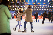 Young couple in love Caucasian man with blond hair with long hair and beard and beautiful woman have fun, active date ice skating on the ice arena in the evening city square in winter on Christmas Eve