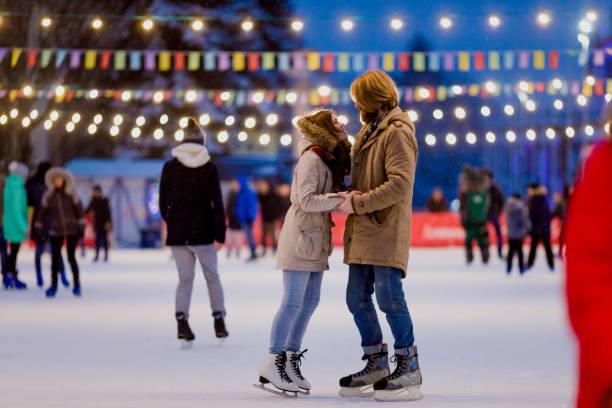 Young couple in love Caucasian man with blond hair with long hair and beard and beautiful woman have fun, active date skating on ice scene in town square in winter on Christmas Eve Young couple in love Caucasian man with blond hair with long hair and beard and beautiful woman have fun, active date ice skating on the ice arena in the evening city square in winter on Christmas Eve ice skating stock pictures, royalty-free photos & images